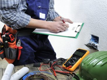 Young electrician at work on switches and sockets of a residential electrical installation.