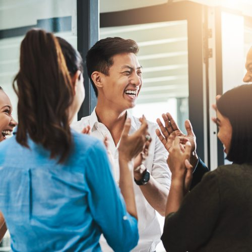 Shot of a group of young businesspeople standing together and clapping in a modern office