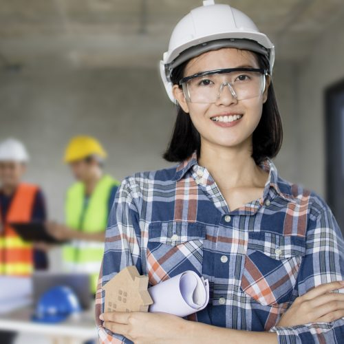 portrait of engineering women at construction site with worker working behind background